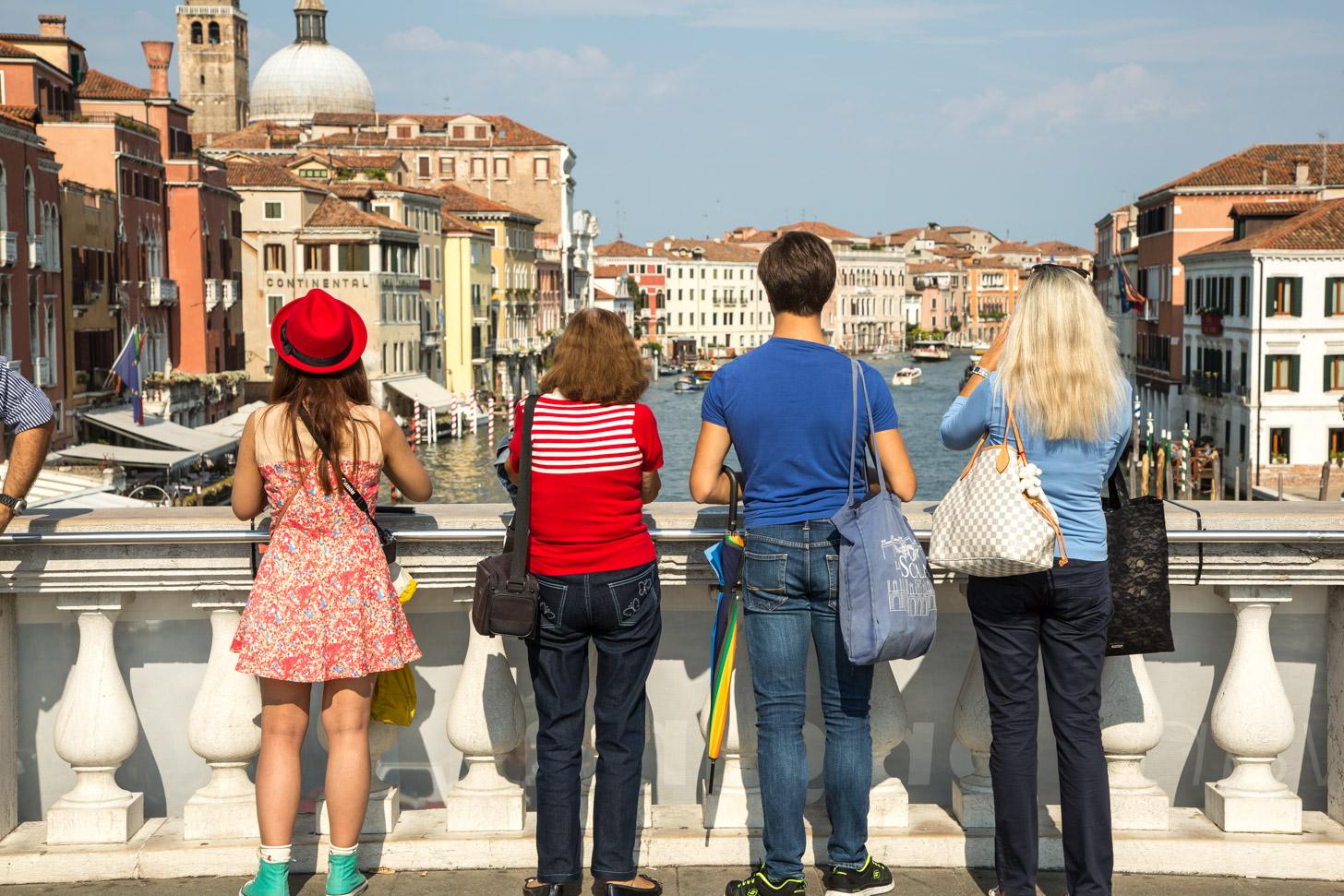Toeristen kijken uit over het Canal Grande in Venetië